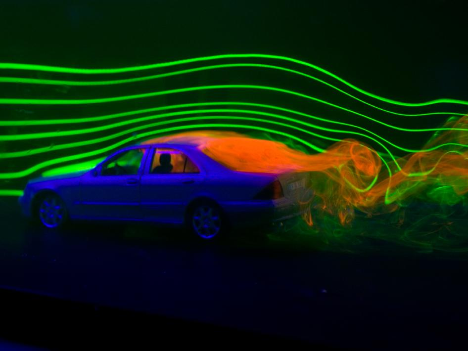 The orange liquid behind the car illustrates the drag for the car. The green lines across illustrate the air moving across the car.