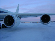 The left wing and engines of NASA's DC-8 are visible as it sits on the tarmac in Thule, Greenland.