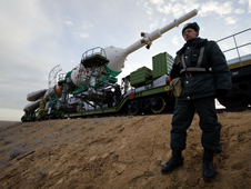 201003310010hq -- A Russian security officer stands guard as the Soyuz TMA-18 spacecraft is rolled out by train