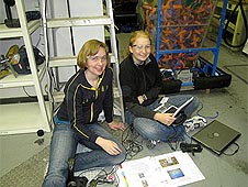 Two girls sit using a laptop computer
