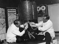 Engineers making adjustments to the Intelsat I (Early Bird) satellite.