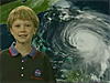A girl stands in front of a picture of a hurricane