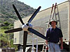 Man stands near a wind turbine