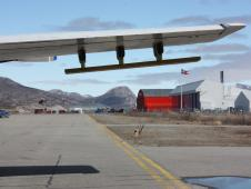 One wing of NASA's P-3B aircraft is visible as it sits on the airstrip in Kangerlussuaq, Greenland with airport buildings on the right.