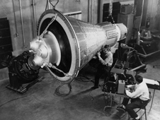 Engineers inspect and test a boilerplate Mercury space capsule.