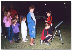 Second-grader Jeremy Hartley brings his telescope to Saturn Observation Campaign.