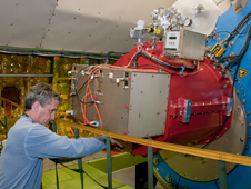 Cornell University mechanical engineer Chuck Henderson makes adjustments on the Faint Object Infrared Camera for the SOFIA Telescope (FORCAST) during line operations testing