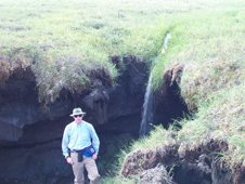 Hinzman stands in front of a permafrost hole.