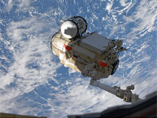 The Russian-built Mini-Research Module 1 is removed from Atlantis' payload bay.