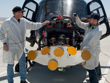 Brian Lataille of Wolfe Air Aviation and Charles Fisher of JPL prepare the engineering model of the Mars Science Laboratory descent radar on the nose gimbal of a helicopter.