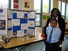 A student and his mother with their project display