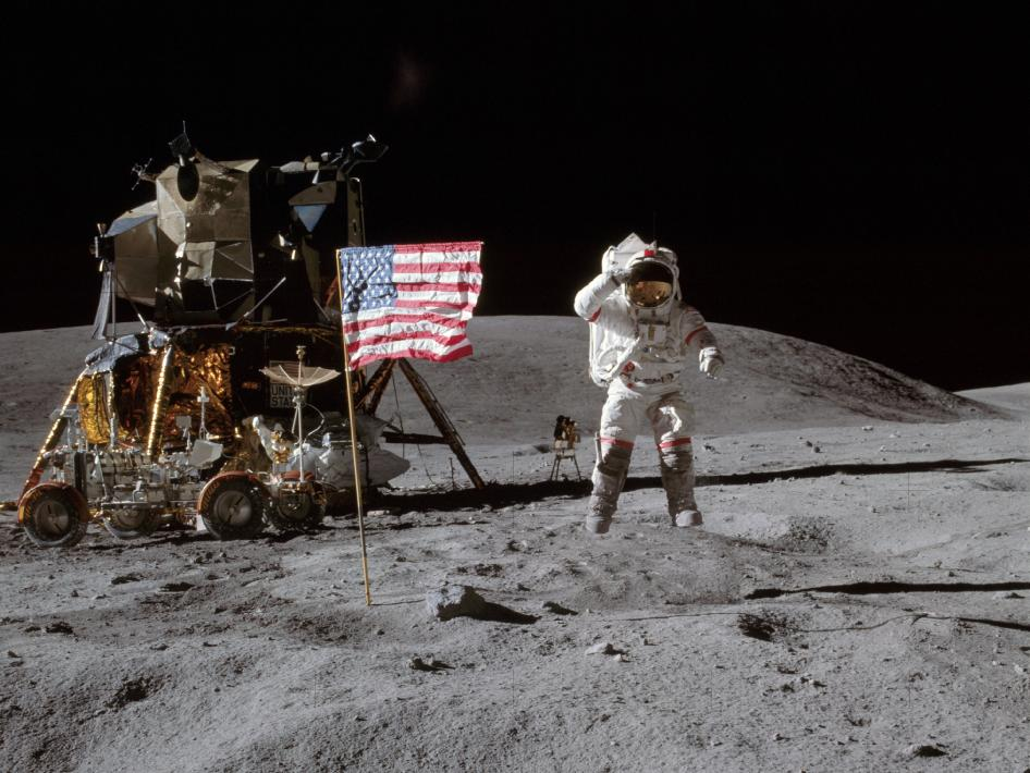 Astronaut John W. Young, commander of the Apollo 16 lunar landing mission, leaps from the lunar surface as he salutes the United States flag at the Descartes landing site during the first Apollo 16 extravehicular activity.