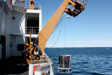 A crane lowers instruments over the side of the Healy into the Chukchi Sea on June 28 to collect water samples and take readings at different depths.
