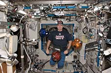 Greg Chamitoff and three small robots floating on the space station