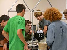 Students looking at a SPHERES robot