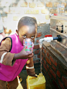 Orphan drinks water from water-treatment system