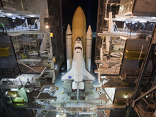 A crawler-transporter begins to roll space shuttle Atlantis out of High Bay 1