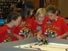 Students in red shirts looking down at a model on a table