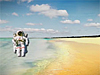 A cartoon astronaut stands on a beach