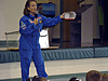 Becky Holden wearing a blue flight suit and talking to students