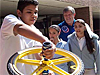Two students and astronaut Roger Crouch watch as a student spins a bicycle wheel gyroscope