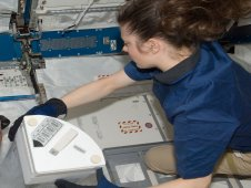 View of Shannon Walker as she works to replace a dewar tray filled with samples