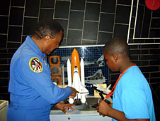 Astronaut Winston Scott and Neil Hawkins look at a model of the space shuttle