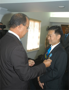 Governor of Aruba Fredis Refunjol presents royal decoration to Cheung