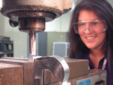 A young woman observes a milling machine
