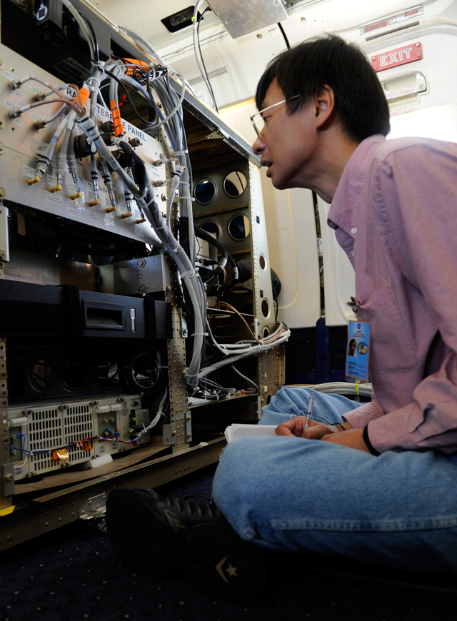 An unidentified researcher looks over the wiring connecting the Airborne Precipitation Radar (APR-2) during a flight aboard the NASA DC-8 aircraft.