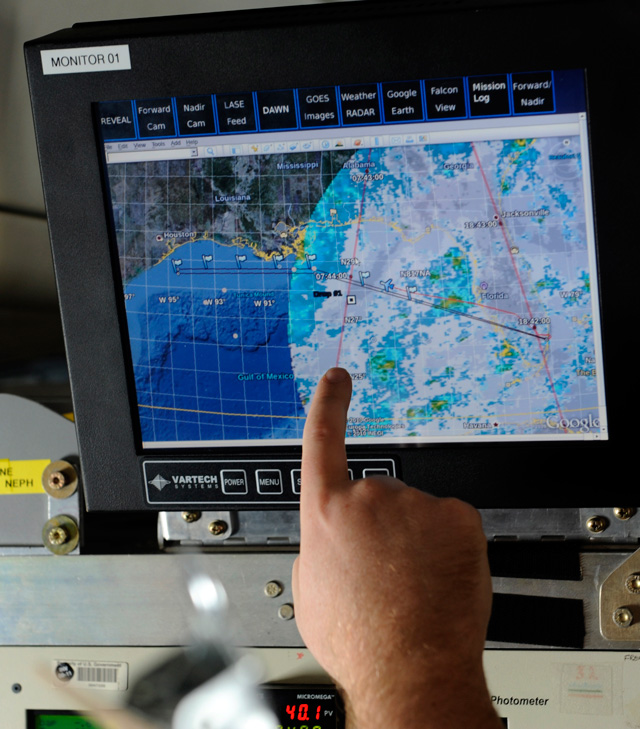 A researcher points out the trajectory of a weather pattern on a computer monitor