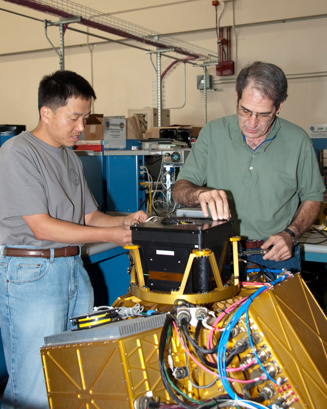 Goddard's Lihau Li, left, and Gerry Heymsfield adjust the High-Altitude Imaging Wind and Rain Profiler prior to its installation