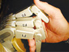 image of machine hand shaking a human hand