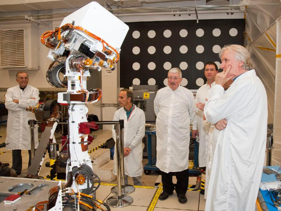 Moviemaker James Cameron and others watch a motioning Curiosity rover