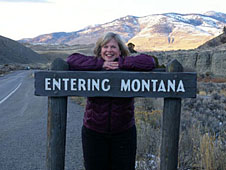 Robbie Lipe standing with an 'Entering Montana' sign