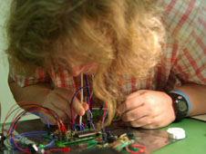 A girl looks closely at a circuit board