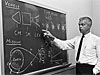 A scientist explains a diagram drawn on a blackboard