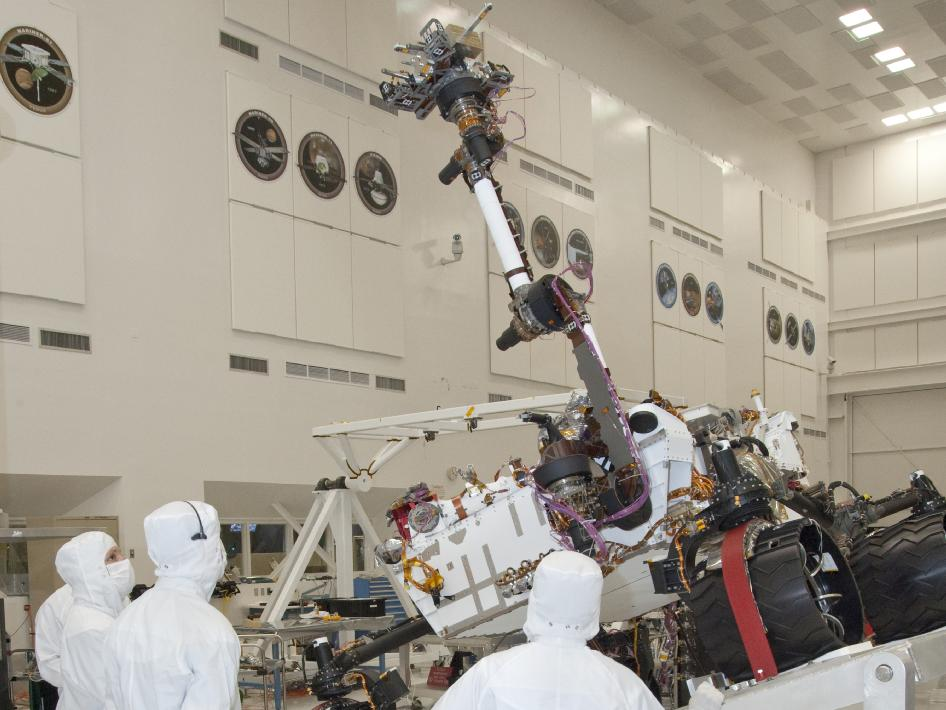 Mars rover, Curiosity, stretches its robotic arm upward in a clean room