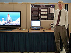 Colin Tilleman with a computer and a monitor showing a space shuttle launch