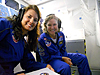 Two teachers inside a mock-up of the space shuttle cockpit