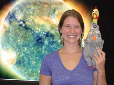 Sarah D. Mitchell poses with SDO mascot Camilla Corona in front of a composite image of our Sun.
