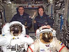 Bill McArthur y Valery Tokarev sostienen trajes espaciales a bordo de la Estacion Espacial Internacional