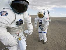 Dos personas con trajes espaciales en terreno arenoso