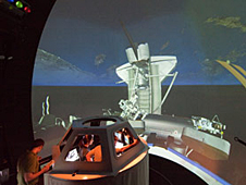 Crew members watch a simulation of the station and shuttle