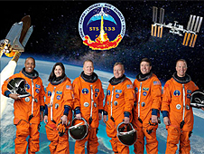 The STS-133 crew poses in orange suits in front of a picture of the shuttle and station over Earth