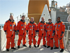 Astronauts pose in orange launch and entry suits