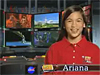 A girl in a red shirt smiles while standing in front of a TV screen