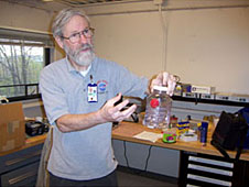 Richard DeLombard holding and explaining a student experiment