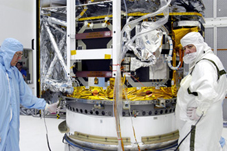 Workers in NASA Spacecraft Hangar AE begin the next phase of processing of the Space Infrared Telescope Facility, which will remain in the clean room until it returns to the pad in early August.