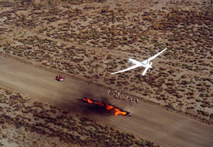 The Unmanned Aerial Vehicles (UAVs) flies over a test fire on a Southern California air strip.